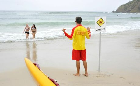 Tom Burns, Byron Bay lifeguard, putting up a sign to warn people not to go swimming at Watego. Sharks have been sighted. Swimmers (LtoR) Maxine Willis and Keeley Thomas of Alstonville are getting out of the water. Mireille Merlet-Shaw