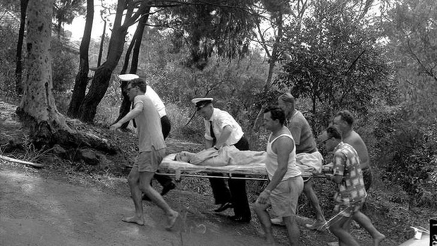 Shark attack victim Marcia Hathaway was carried by stretcher to an ambulance, which broke down and failed to climb the hill despite getting a push. Photo: N. Stubbs